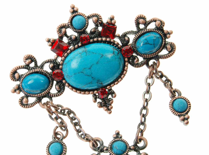 detail of turquoise brooch with red crystals